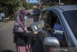 Seorang guru memberikan rapor kepada orang tua siswa saat penerimaan rapor dengan layanan tanpa turun di SMP IT Insan Sejahtera, Kampung Toga, Kabupaten Sumedang, Jawa Barat, Selasa (22/6/2021). Sebanyak 55 siswa kelas 9 tingkat SMP Insan Sejahtera mengikuti pembagian rapor dengan layanan tanpa turun guna mencegah kerumunan di tengah pandemi COVID-19. ANTARA FOTO/Raisan Al Farisi/agr