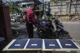 Seorang guru memberikan rapor kepada pengemudi ojek daring saat penerimaan rapor dengan layanan tanpa turun di SMP IT Insan Sejahtera, Kampung Toga, Kabupaten Sumedang, Jawa Barat, Selasa (22/6/2021). Sebanyak 55 siswa kelas 9 tingkat SMP Insan Sejahtera mengikuti pembagian rapor dengan layanan tanpa turun guna mencegah kerumunan di tengah pandemi COVID-19. ANTARA FOTO/Raisan Al Farisi/agr