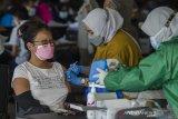 Petugas tenaga kesehatan menyuntikkan Vaksin COVID-19 kepada warga saat vaksinasi massal di Cimahi Techno Park, Cimahi, Jawa Barat, Selasa (22/6/2021). Sedikitnya 2000 warga Kota Cimahi perhari dari usia 18 tahun hingga lansia disuntikkan vaksin COVID-19 dosis pertama guna percepatan vaksinasi yang digelar selama tiga hari oleh Polres Cimahi dan Pemerintah kota Cimahi. ANTARA FOTO/Novrian Arbi/agr