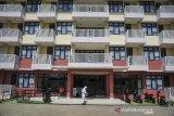 Seorang petugas menyemprotkan cairan disinfektan di halaman Asrama PUPR, Kompleks Kampus Unpad Jatinangor, Kabupaten Sumedang, Jawa Barat, Selasa (22/6/2021). Sekda Kabupaten Sumedang Herman Suryatman menyatakan, untuk mengantisipasi lonjakan kasus COVID-19 dan penuhnya Rumah Sakit di Kabupaten Sumedang, pihaknya akan menyiapkan Rumah Sakit darurat untuk pasien terkonfirmasi positif COVID-19 yang diantaranya adalah di Asrama PUPR Kampus Unpad. ANTARA FOTO/Raisan Al Farisi/agr