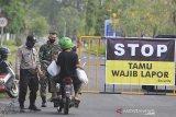 Petugas keamanan dibantu personel TNI memeriksa warga yang akan masuk di salah satu kompleks perumahan yang melakukan karantina wilayah di Indramayu, Jawa Barat, Rabu (23/6/2021). Karantina wilayah dilakukan untuk membatasi kegiatan masyarakat di lingkungan itu dan memutus mata rantai penyebaran COVID-19. ANTARA FOTO/Dedhez Anggara/agr