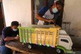 Perajin melakukan proses pewarnaan pada miniatur truk di Desa Pohrubuh, Kediri, Jawa Timur, Rabu (23/6/2021). Kerajinan berbahan baku kayu jati tersebut dipasarkan melalui media sosial seharga Rp500 ribu hingga Rp1 juta per unit tergantu ukuran. Antara Jatim/Prasetia Fauzani/zk