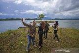 Pengunjung berswafoto dengan latar belakang Waduk Riam Kanan di Kawasan Wisata Bukit Batu, Desa Sungai Luar Tiwingan Baru, Kabupaten Banjar, Kalimantan Selatan, Rabu (23/6/2021). Wisata Bukit Batu yang terletak di kawasan waduk Riam Kanan itu  menjadi salah satu destinasi wisata alam yang menawarkan pemandangan Pegunungan Meratus dan waduk Riam Kanan serta memiliki fasilitas umum musala yang ramai di kunjungi wisatawan lokal. Foto Antaranews Kalsel/Bayu Pratama S.