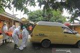 Petugas membawa jenazah yang meninggal dunia di rumah untuk dimakamkan dengan protokol COVID-19 di Kelurahan Kepandean, Indramayu, Jawa Barat, Kamis (24/6/2021). Satgas penanganan COVID-19 melaporkan kasus konfirmasi positif hingga Rabu (23/6/2021) meningkat mencapai 2.033.421 kasus sedangkan kasus meninggal akibat COVID-19 menembus 55.594 jiwa. ANTARA FOTO/Dedhez Anggara/agr
