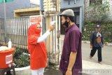 Relawan SIBAT Palang Merah Indonesia (PMI) lakukan pemeriksaan suhu tubuh pada seorang warga di Cisarua, Jawa Barat. Antara/HO/PMI/IFRC).