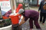 Relawan SIBAT Palang Merah Indonesia (PMI) memberi edukasi mencuci tangan yang baik dan benar kepada seorang warga di Cisarua, Jawa Barat. Antara/HO/PMI/IFRC).