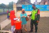 Relawan SIBAT Palang Merah Indonesia (PMI) didampingi Satgas COVID-19 dari TNI sedang memberi edukasi mencuci tangan yang baik dan benar kepada seorang warga di Cisarua, Jawa Barat. Antara/HO/PMI/IFRC).
