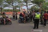 Petugas gabungan TNI/Polri menghentikan pengendara motor yang tidak menggunakan masker saat razia di Indramayu, Jawa Barat, Kamis (24/6/2021). Razia masker tersebut digelar untuk meningkatkan kesadaran masyarakat untuk tetap menerapkan protokol kesehatan sebagai upaya pencegahan penyebaran COVID-19. ANTARA FOTO/Dedhez Anggara/agr