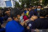 Sejumlah mahasiswa membawa temannya yang pingsan saat aksi unjuk rasa di kawasan Jalan Lambung Mangkurat, Banjarmasin, Kalimantan Selatan, Kamis (24/6/2021). Aksi menyerukan menolak adanya pelemahan terhadap lembaga antirasuah, Komisi Pemberantasan Korupsi (KPK) tersebut sempat terjadi kericuhan akibat Ketua DPRD Kalsel Supian HK yang tak kunjung datang menemui para demonstran, sesuai tuntutan mereka. Foto Antaranews Kalsel/Bayu Pratama S.