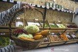 Pengunjung membawa sejumlah sayuran di dalam keranjang untuk dibeli di Alifmart Store, Bandung, Jawa Barat, Kamis (24/6/2021). Toko sayuran tersebut menjual sedikitnya 64 jenis komoditas  sayuran hasil pertanian yang dibawa langsung dari kelompok tani Pondok Pesantren yang ada di Jawa Barat sebagai salah satu sektor usaha pemberdayaan dan peningkatan ekonomi bagi pertani. ANTARA FOTO/Novrian Arbi/agr