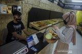 Pengunjung bertransaksi  untuk membayar sejumlah sayuran yang dijual di Alifmart Store, Bandung, Jawa Barat, Kamis (24/6/2021). Toko sayuran tersebut menjual sedikitnya 64 jenis komoditas  sayuran hasil pertanian yang dibawa langsung dari kelompok tani Pondok Pesantren yang ada di Jawa Barat sebagai salah satu sektor usaha pemberdayaan dan peningkatan ekonomi bagi pertani. ANTARA FOTO/Novrian Arbi/agr