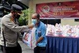 Polisi menyerahkan bantuan paket sembako kepada warga saat kegiatan bakti sosial di Denpasar, Bali, Jumat (25/6/2021). Bakti sosial serentak tersebut diselenggarakan dalam rangka Hari Bhayangkara ke-75 untuk membantu masyarakat khususnya warga yang perekonomiannya terdampak pandemi COVID-19. ANTARA FOTO/Fikri Yusuf/nym.