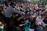 Anggota Polisi mengarahkan ribuan warga yang antre vaksinasi COVID-19 massal di Denpasar, Bali, Sabtu (26/6/2021). Petugas Kepolisian berupaya menertibkan masyarakat yang membludak saat mengikuti vaksinasi massal yang digelar di ruang publik tersebut untuk mencegah kerumunan dan agar tetap menerapkan protokol kesehatan COVID-19. ANTARA FOTO/Nyoman Hendra Wibowo/nym.