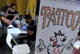 Seniman tato merajah tubuh pengunjung saat kegiatan Kuta Tattoo Fest 2021 di kawasan Kuta, Badung, Bali, Sabtu (26/6/2021). Kegiatan yang diikuti seniman dan studio tato dari berbagai daerah di Indonesia tersebut diselenggarakan untuk mengembangkan industri seni tato serta membantu pemulihan sektor perekonomian dan pariwisata di Bali yang terdampak pandemi COVID-19. ANTARA FOTO/Fikri Yusuf/nym.