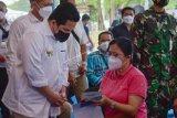 Menteri BUMN Erick Thohir (kiri) berbincang dengan warga saat meninjau pelaksanaan vaksininasi massal COVID-19 di Sentra Vaksinasi Bersama BUMN di Lanud Soewondo, Kota Medan, Sabtu (26/6/2021). Program vaksinasi massal bersama BUMN ini diharapkan dapat meningkatkan percepatan vaksinasi COVID-19 di Provinsi Sumatera Utara, dengan target sebanyak 5.000 orang per hari ANTARA FOTO/Fransisco Carolio/Lmo/rwa