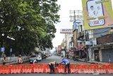 Petugas Dinas Perhubungan dan Polisi menyusun pembatas jalan saat penutupan pusat Kota di Jalan KHZ Mustofa, Kota Tasikmalaya, Jawa Barat, Minggu (27/6/2021). Pemerintah Kota Tasikmalaya melakukan langkah tegas menutup jalan di pusat kota atau pertokoan untuk mengantisipasi kerumunan dan mengurangi aktivitas warga di tengah lonjakan kasus COVID-19. ANTARA FOTO/Adeng Bustomi/agr