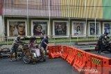 Tukang becak menerobos pembatas jalan saat penutupan pusat kota di Jalan KHZ Mustofa, Kota Tasikmalaya, Jawa Barat, Minggu (27/6/2021). Pemerintah Kota Tasikmalaya melakukan langkah tegas menutup jalan di pusat kota atau pertokoan untuk mengantisipasi kerumunan dan mengurangi aktivitas warga di tengah lonjakan kasus COVID-19. ANTARA FOTO/Adeng Bustomi/agr