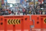 Warga berswafoto di jalan yang lengang saat penutupan pusat kota di Jalan KHZ Mustofa, Kota Tasikmalaya, Jawa Barat, Minggu (27/6/2021). Pemerintah Kota Tasikmalaya melakukan langkah tegas menutup jalan di pusat kota atau pertokoan untuk mengantisipasi kerumunan dan mengurangi aktivitas warga di tengah lonjakan kasus COVID-19. ANTARA FOTO/Adeng Bustomi/agr