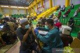 Petugas kesehatan menyuntikkan vaksin COVID-19 pada warga saat vaksinasi COVID-19 massal di GOR Hasanuddin HM, Banjarmasin, Kalimantan Selatan, Sabtu (26/6/2021). Dinas Kesehatan bersama TNI dan POLRI menggelar vaksinasi COVID-19 massal dalam rangka satu juta vaksin yang menjadi program pemerintah pusat dengan sasaran lansia, pralansia, guru/dosen, ODGJ, disabilitas, masyarakat umum dan masyarakat rentan untuk mencapai kekebalan komunal atau herd immunity menuju Indonesia sehat bebas COVID-19. Foto Antaranews Kalsel/Bayu Pratama S.