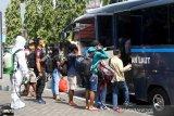 Sejumlah pekerja PT Nusa Halmahera Minerals (NHM) dikawal oleh petugas dengan pakaian APD  saat menaiki di bus TNI AL menuju hotel untuk menjalani isolasi karena terkonfirmasi positif COVID-19, di Kota Ternate, Provinsi Maluku Utara,  Minggu (27/06/2021). Berdasarkan data Dinas Kesehatan Kabupaten Halmahera Utara, Provinsi Maluku Utara, ada 307 pasien yang merupakan kasus aktif COVID-19 di daerah itu dengan 251 orang diantaranya adalah pekerja di perusahaan tambang emas PT Nusa Halmahera Minerals (NHM). ANTARA FOTO/ Harmoko Minggu