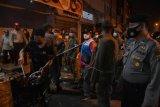 Petugas gabungan dari Kepolisian dan Satpol PP meminta pengunjung dan pemilik lokasi usaha kuliner yang melewati batas aturan waktu operasional untuk membubarkan diri saat sidak penerapan Pemberlakuan Pembatasan Kegiatan Masyarakat (PPKM) Mikro di Jalan Semarang, Simpang Kepandu, Kota Medan, Sumatera Utara, Sabtu (26/6/2021) malam. Operasi Yustisi di pusat-pusat keramaian di kota Medan tersebut bertujuan untuk menertibkan berbagai lokasi kegiatan usaha agar mengikuti aturan PPKM Mikro serta memastikan pelaksanaan protokol kesehatan untuk mencegah penyebarah wabah COVID-19. ANTARA FOTO/Fransisco Carolio/Lmo/aww.
