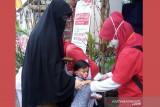 Relawan SIBAT PMI melakukan pengukuran suhu pada anak di Cisarua, Bogor, Jawa Barat. (Antara/HO/PMI/IFRC).