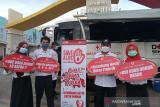 Petugas PMI Kota Cilegon melakukan sosialisasi edukasi pentingnya untuk mendonorkan darah dengan poster di depan mobil unit donor darah Kota Cilegon, Banten. (Antara/HO/PMI/IFRC).