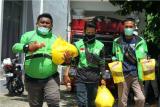 Sejumlah pengendara ojek membawa paket bahan pokok usai mengikuti vaksinasi COVID-19 di Bele Li Mbui, Kota Gorontalo, Gorontalo, Kamis (8/7/2021). Pemerintah Provinsi Gorontalo memberikan hadiah paket bahan kebutuhan pokok bagi pengemudi becak motor (bentor) dan ojek daring yang telah melakukan dua kali suntikan vaksin. ANTARA FOTO/Adiwinata Solihin/foc.