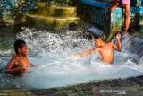 Sejumlah anak-anak bermain di Pemandian Air Wailatu di Negeri Tulehu, Kabupaten Maluku Tengah, Provinsi Maluku, Kamis (8/7/2021). Pemandian Air Wailatu adalah kolam yang berasal dari mata air di Negeri Tulehu, yang menjadi digunakan masyarakat setempat untuk mandi, mencuci, sumber air minum dan tempat wisata.  (ANTARA FOTO/FB Anggoro)