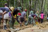Prajurit TNI dan warga bergotong royong membangun jalan desa saat program Tentara Manunggal Membangun Desa (TMMD) di Desa Suato Lama, Kabupaten Tapin, Kalimantan Selatan, Senin (12/7/2021). Kodim 1010/Tapin melaksanakan program TMMD ke 111 dengan membangun jalan desa sepanjang 3.149 meter, merenovasi mushola, poskamling dan rumah warga guna meningkatkan perekonomian masyarakat sekaligus membantu pemerintah dalam percepatan pembangunan serta dilokasi TMMD tersebut dilaksanakan sosialisasi stunting, wawasan kebangsaan, protokol kesehatan dan vaksinasi massal. Foto Antaranews Kalsel/Bayu Pratama S.