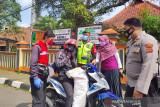 Relawan PMI, petugas kepolisian dan aparat Kelurahan Benteng, memberikan edukasi untuk kurangi mobilitas dan pentingnya penggunaan masker kepada pengandara sepeda motor  di depan SDN Benteng 1, Kecamatan Warudoyong, Kota Sukabumi, Jawa Barat. (Antara/HO/PMI/IFRC).