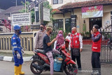 Relawan PMI, petugas kepolisian dan aparat Kelurahan Benteng, memberikan edukasi untuk kurangi mobilitas dan pentingnya penggunaan masker kepada pengandara sepeda motor di depan Kantor Kelurahan Benteng, Kecamatan Warudoyong, Kota Sukabumi, Jawa Barat.  (Antara/HO/PMI/IFRC).