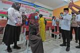 Gubernur Jambi Al Haris (kanan) menyemangati seorang pelajar yang akan menerima suntikan vaksin saat meninjau vaksinasi COVID-19 di SMA Adhyaksa 1 Jambi, Jambi, Rabu (14/7/2021). Vaksinasi massal yang menargetkan pelajar dan guru di lingkungan sekolah di bawah naungan Ikatan Adhyaksa Dharmakarini wilayah Jambi tersebut bagian dari sinergitas dan upaya lintas instansi untuk menekan jumlah kasus COVID-19 yang kembali naik dalam beberapa hari terakhir di daerah itu. ANTARA FOTO/Wahdi Septiawan/wsj.