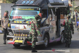 Petugas gabungan TNI dan Polri memeriksa kendaraan yang melintas di jalur Pantura Perbatasan Indramayu-Cirebon, Jawa Barat, Sabtu (17/7/2021). Penyekatan tersebut untuk membatasi mobilitas warga yang keluar masuk antara kabupaten Indramayu dan Cirebon terutama saat akhir pekan. ANTARA FOTO/Dedhez Anggara/agr