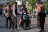 Anggota Polisi menindak warga negara asing (WNA) yang tidak menggunakan masker saat operasi yustisi Pemberlakukan Pembatasan Kegiatan Masyarakat (PPKM) Darurat di kawasan wisata Canggu, Badung, Bali, Senin (19/7/2021). Operasi yustisi yang digelar di kawasan pariwisata tersebut untuk mendisiplinkan masyarakat dan WNA agar mentaati peraturan protokol kesehatan khususnya penggunaan masker saat beraktivitas selama PPKM Darurat sebagai upaya mencegah penyebaran COVID-19. ANTARA FOTO/Nyoman Hendra Wibowo/nym.