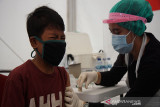 Ekspresi seorang anak saat disuntik vaksin COVID-19 oleh petugas PMI. (Antara/HO/PMI/IFRC).