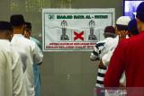 Spanduk himbauan jaga jarak terpampang di Masjid Al Fatah saat warga melaksanakan shalat Ied dengan menjaga jarak dan mengenakan masker pada Hari Raya Idul Adha di Kota Ambon, Provinsi Maluku, Selasa (20/7/2021). Pemerintah Provinsi Maluku mengizinkan warga Muslim untuk beribadah shalat Ied berjamaah di masjid pada Hari Raya Idul Adha 1442 Hijriah dengan menerapkan protokol kesehatan untuk mencegah penyebaran pandemi COVID-19. (ANTARA FOTO/FB Anggoro)