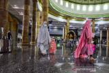 Seorang ibu dan anaknya mengenakan masker usai shalat Ied berjamaah pada Hari Raya Idul Adha di Masjid Al Fatah, Kota Ambon, Provinsi Maluku, Selasa (20/7/2021). (ANTARA FOTO/FB Anggoro)