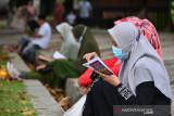 ZIARAH MAKAM TSUNAMI IDUL ADHA. Warga berdoa dilanjutkan menaburkan bunga saat ziarah di makam masal Tsunami, Desa Ulee Lheue, Banda Aceh, Aceh, Selasa (20/7/2021). Pemerintah Aceh mengizinkan masyarakat melaksanakan ziarah makam dan kegiataan keagaman  shalat Idul Adha 1442 Hijriyah sesuai dengan Tausiah Majelis Permusyawaratan Ulama (MPU) Aceh dengan menerapkan  protokol kesehatan secara ketat. ANTARA FOTO/Ampelsa.ANTARA FOTO/AMPELSA (ANTARA FOTO/AMPELSA)