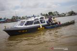 Kasat Polair Polresta Banjarmasin AKP Christugus Lirens (tengah) menyerahkan daging kurban kepada warga di Sungai Barito, Banjarmasin, Kalimantan Selatan, Rabu (21/7/2021). Satuan Polisi Air (Satpolair) Polresta Banjarmasin membagikan daging kurban pada H+2 Hari Raya Idul Adha 1442 H dengan cara membagikan langsung kepada warga yang beraktivitas di alur Sungai Barito untuk menghindari terjadinya kerumunan warga serta meminimalisir penyebaran COVID-19. Foto Antaranews Kalsel/Bayu Pratama S.