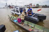 Kasat Polair Polresta Banjarmasin AKP Christugus Lirens (kanan) menyerahkan daging kurban kepada warga di Sungai Barito, Banjarmasin, Kalimantan Selatan, Rabu (21/7/2021). Satuan Polisi Air (Satpolair) Polresta Banjarmasin membagikan daging kurban pada H+2 Hari Raya Idul Adha 1442 H dengan cara membagikan langsung kepada warga yang beraktivitas di alur Sungai Barito untuk menghindari terjadinya kerumunan warga serta meminimalisir penyebaran COVID-19. Foto Antaranews Kalsel/Bayu Pratama S.