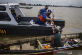 Kasat Polair Polresta Banjarmasin AKP Christugus Lirens menyerahkan daging kurban kepada warga di Sungai Barito, Banjarmasin, Kalimantan Selatan, Rabu (21/7/2021). Satuan Polisi Air (Satpolair) Polresta Banjarmasin membagikan daging kurban pada H+2 Hari Raya Idul Adha 1442 H dengan cara membagikan langsung kepada warga yang beraktivitas di alur Sungai Barito untuk menghindari terjadinya kerumunan warga serta meminimalisir penyebaran COVID-19. Foto Antaranews Kalsel/Bayu Pratama S.