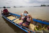Warga menunjukkan daging kurban yang dibagikan Satpolair Polresta Banjarmasin di Sungai Barito, Banjarmasin, Kalimantan Selatan, Rabu (21/7/2021). Satuan Polisi Air (Satpolair) Polresta Banjarmasin membagikan daging kurban pada H+2 Hari Raya Idul Adha 1442 H dengan cara membagikan langsung kepada warga yang beraktivitas di alur Sungai Barito untuk menghindari terjadinya kerumunan warga serta meminimalisir penyebaran COVID-19. Foto Antaranews Kalsel/Bayu Pratama S.