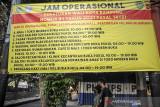 Warga melintas di samping spanduk pengumuman jam operasional di salah satu pusat perbelanjaan di Kota Bandung, Jawa Barat, Rabu (21/7/2021). Menindaklanjuti arahan Presiden Joko Widodo, Pemerintah Kota Bandung kembali memperpanjang PPKM hingga 25 Juli mendatang dengan melonggarkan beberapa kebijakan guna mencegah penyebaran COVID-19. ANTARA FOTO/Raisan Al Farisi/agr