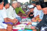 Warga menyantap hidangan yang disajikan di atas nampan bulat khas Melayu Jambi dalam tradisi