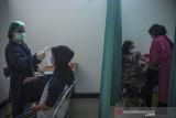 Tenaga kesehatan memeriksa suhu tubuh seorang warga yang akan menjalani vaksinasi COVID-19 di Puskesmas Jajaway, Bandung, Jawa Barat, Kamis (22/7/2021). Sebanyak 80 Puskesmas di Kota Bandung memberikan layanan vaksinasi bagi warga setempat sebagai salah satu langkah percepatan program vaksinasi nasional. ANTARA FOTO/Raisan Al Farisi/agr
