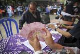 Petugas menunjukan uang tunai saat pembagian bantuan sosial tunai di Jajaway, Antapani Kidul, Bandung, Jawa Barat, Kamis (22/7/2021). Gubernur Jawa Barat, Ridwan Kamil mengatakan, bantuan sosial dari pemerintah pusat bagi warga terdampak PPKM di Jawa Barat mengalami peningkatan dari sekitar 40 persen menjadi 64 persen dari total penduduk Jawa Barat. ANTARA FOTO/Raisan Al Farisi/agr