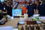 Petugas kepolisian menunjukkan tersangka berinisial ST (tengah) dan barang bukti narkoba jenis ekstasi saat konferensi pers di Polresta Denpasar, Bali, Kamis (22/7/2021). Satresnarkoba Polresta Denpasar mengamankan sejumlah peralatan produksi ekstasi rumahan, 286 butir ekstasi siap edar dan serbuk ekstasi seberat 106 gram yang diproduksi tersangka ST setelah belajar dari internet. ANTARA FOTO/Fikri Yusuf/nym.