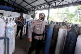 Petugas kepolisian berjaga di PT Samator, Mengwi, Badung, Bali, Kamis (22/7/2021). Sejumlah personel Satbrimob dan Ditlantas Polda Bali dilibatkan untuk menjaga dan mengawal proses pendistribusian oksigen medis menuju ke sejumlah rumah sakit di wilayah Bali guna memastikan proses distribusi itu berjalan lancar dan aman. ANTARA FOTO/Fikri Yusuf/nym.