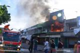 KEBAKARAN TOKO PEDAGANG DI PASAR LAMBARO. Petugas berusaha memadamkan kobaran api saat kebakaran toko pedagang di Pasar Lambaro, Kabupaten Aceh Besar, Aceh, Jumat (23/7/2021). Kebakaran tiga toko pedagang itu berawal dari kobaran api pada bagian belakang bangunan, tidak ada korban jiwa dalam musibah tersebut karena pemilik toko tidak berada di tempat dan api berhasil dipadamkan setelah lima unit mobil kebakaran dikerahkan ke lokasi kejadian. ANTARA FOTO/Ampelsa.